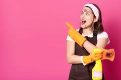 Energische schlanke Hausfrau mit breitem ge?ffnetem Mund, beiseite schauend und heben Hand an und zeigen Richtung mit dem Zeigefi stockfotos