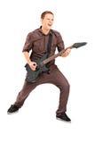 Energischer junger Mann, der auf E-Gitarre spielt Lizenzfreies Stockfoto