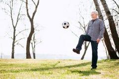 Energischer reifer Mann, der mit Ball spielt stockfotos