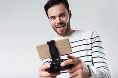 Energized bearded man using portable gamepad Royalty Free Stock Image