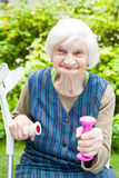 Energized elderly woman doing exercises with dumbbells Royalty Free Stock Images