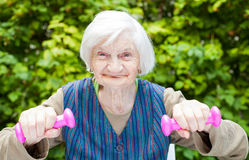 Energized elderly woman doing exercises with dumbbells Stock Photos