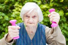 Energized elderly woman doing exercises with dumbbells Stock Image