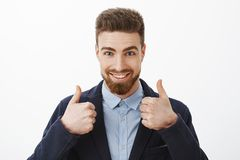 Energized good-looking and assured successful man with beard and blue eyes in stylish formal suit showing thumbs up. Being assured plan work great standing self stock photo