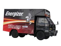 Energizer Van Isolated. A Daihatsu Delta delivery van with the Energizer battery advertisement painted around its side Stock Photography