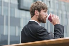 Energizing sip of coffee. Young businessman sitting on a bench and drinking beverage Stock Image