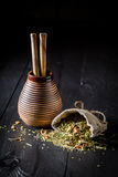 Energizing yerba mate made of fresh dried leaves. On dark table Royalty Free Stock Photography