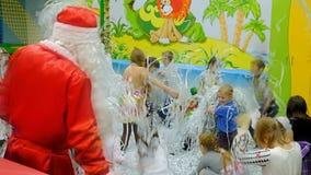 Energodar, Ukraine - 29 December 2017: Children`s festival. A children with Santa Claus play with confetti. Energodar, Ukraine - 29 December 2017: Children`s stock footage