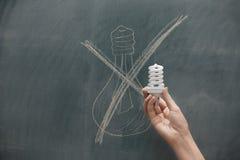 Energooszczędny - ręka trzyma energooszczędną żarówkę Obrazy Royalty Free