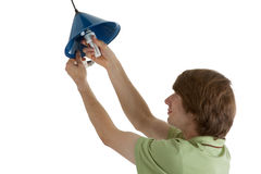 Energy. Young man, installed an energy saving lamp royalty free stock images