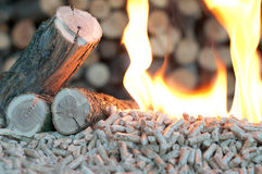 Energy. Oak Pellets in  flames- chopped firewood background Royalty Free Stock Photo