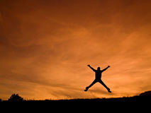 Energy. Silhouette man jumping on orange sunset royalty free stock images