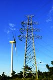 Energy. Wind-driven generator and transmission tower under blue sky Royalty Free Stock Image