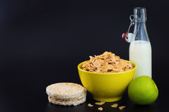 Energy breakfast for diet cereal flakes of corn milk and green apple on black background. With copy space stock image