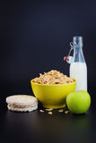 Energy breakfast for diet cereal flakes of corn milk and green apple on black background. With copy space stock photos