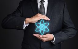 Free Energy Concept. Closeup Of An Unrecognizable Businessman With Cupped Hands Around A Neon Blue Glowing Nuclear Icon Stock Image - 208529751