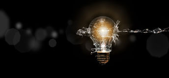 Energy Concept. Spray of water against a light bulb Stock Photography