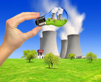 Energy concepts. Hand holding bulb with nuclear power plant Royalty Free Stock Photos