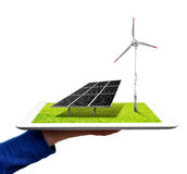 Energy concepts. Hand holding a tablet with a wind turbine and solar panel Stock Photography