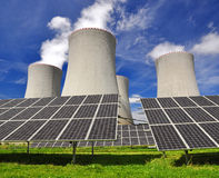 Energy concepts. Solar energy panels before a nuclear power plant Stock Photos