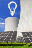 Energy concepts. Solar energy panels before a nuclear power plant and bulb from clouds Royalty Free Stock Photos