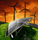 Energy concepts. Solar energy panels with wind turbines in the setting sun Stock Photography