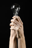 Energy consumption and energy saving topic: human hand holding a light bulb on black background in studio Stock Images