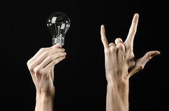 Energy consumption and energy saving topic: human hand holding a light bulb on black background in studio Royalty Free Stock Photography