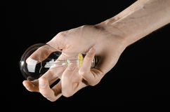 Energy consumption and energy saving topic: human hand holding a light bulb on black background in studio Stock Image