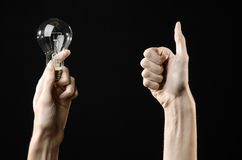 Energy consumption and energy saving topic: human hand holding a light bulb on black background in studio Stock Photos