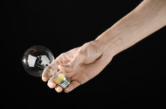 Energy consumption and energy saving topic: human hand holding a light bulb on black background in studio Royalty Free Stock Photos