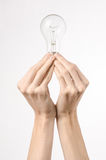 Energy consumption and energy saving topic: human hand holding a light bulb on a white background in studio Royalty Free Stock Photos