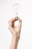 Energy consumption and energy saving topic: human hand holding a light bulb on a white background in studio Stock Photos