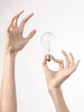 Energy consumption and energy saving topic: human hand holding a light bulb on a white background in studio Stock Image
