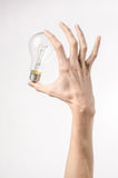 Energy consumption and energy saving topic: human hand holding a light bulb on a white background in studio Stock Photography