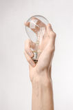 Energy consumption and energy saving topic: human hand holding a light bulb on a white background in studio Royalty Free Stock Images