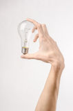 Energy consumption and energy saving topic: human hand holding a light bulb on a white background in studio Stock Photo