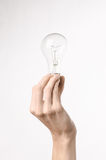 Energy consumption and energy saving topic: human hand holding a light bulb on a white background in studio Royalty Free Stock Photo