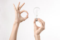 Energy consumption and energy saving topic: human hand holding a light bulb on a white background in studio Royalty Free Stock Photography