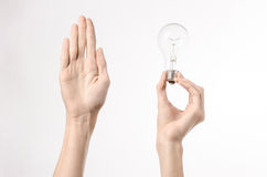 Energy consumption and energy saving topic: human hand holding a light bulb on a white background in studio. Energy consumption and energy saving topic: human royalty free stock images