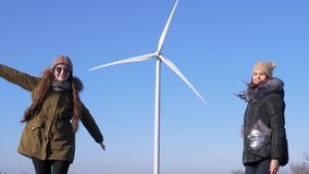 Energy conversion, cheerful friends have fun near wind turbine against blue sky. Outside stock video footage
