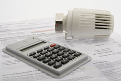 Energy costs. Accounting with thermostat and pocket calculator Royalty Free Stock Image