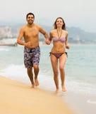 Energy couple running on the sea beach Stock Photo