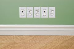 Energy Crisis Concept Outlets. New hardwood flooring, baseboard molding and green wall with extra power outlets (energy crisis concept Stock Images