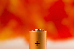 Energy. Detail of a battery with plus sign on orange background Stock Photo