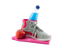 Energy drink in a sneaker. Blue collored energy drink in a grey sneaker on a pink towel Royalty Free Stock Images