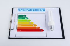 Energy efficiency concept with energy rating chart. And Energy savings lamp royalty free stock photo