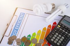 Energy efficiency concept with energy rating chart. And Energy savings lamp, coin, calculator stock image