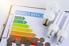 Energy efficiency concept with energy rating chart. And Energy savings lamp, coin royalty free stock photo