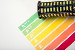 Energy efficiency concept with energy rating chart and LED lamp stock image